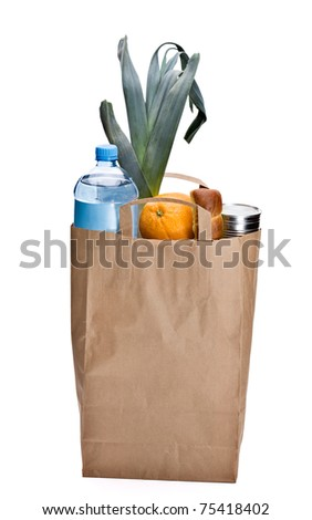 Fresh groceries in a brown bag. Including bread, orange, water, can and leek