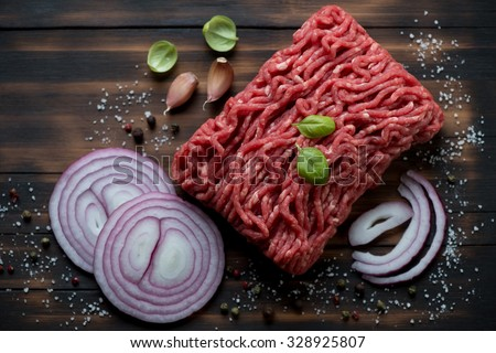 Fresh ground beef meat with seasonings, rustic wooden surface