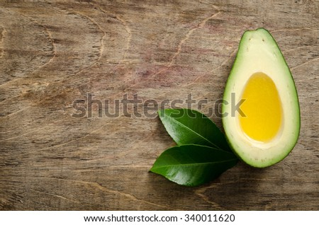 fresh half avocado like a bowl for oil on wooden background. - stock photo