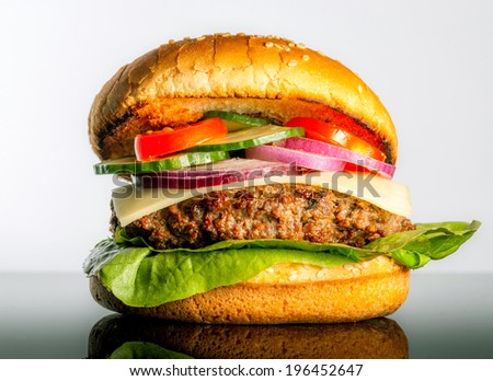Fresh hamburger with many vegetables on black reflex background