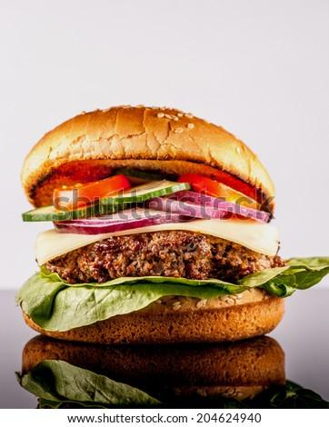 Fresh hamburger with many vegetables on black reflex background - stock photo