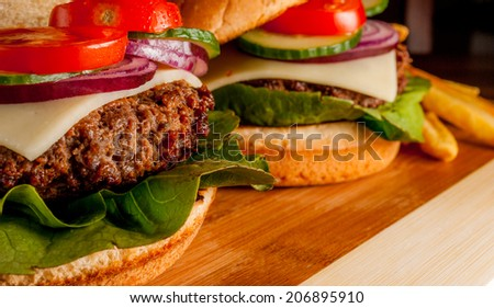 Fresh hamburger with vegetables and fries on wood plate