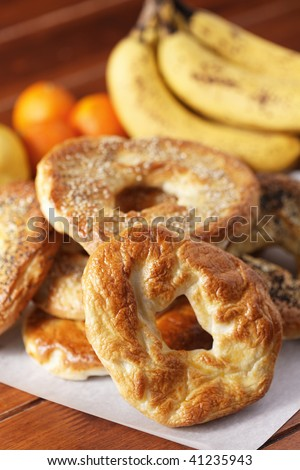fresh handmade bagel for the breakfast with fruit in the background. Very shallow depth of field. - stock photo