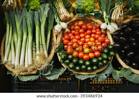 Fresh harvest in basket beautifully presented outside on market for sale: tomatoes, leek, zucchini, cabbage, garlic, etc - stock photo
