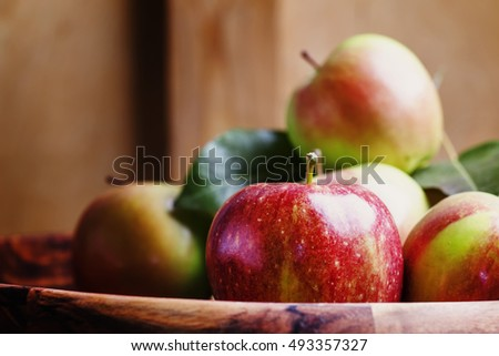 Fresh harvest of autumn sweet apples in a large bowl with hay on a vintage wooden background, selective focus and shallow depth of field