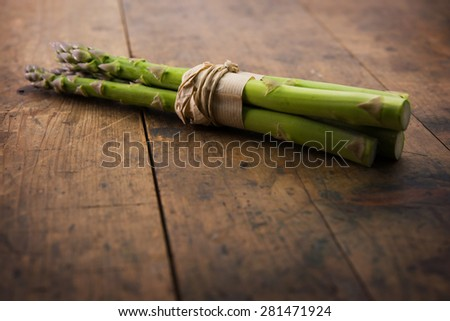 Fresh harvested asparagus, on a old wooden table. Shallow depth of field. - stock photo