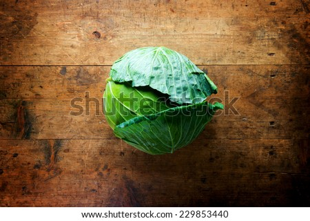 Fresh harvested cabbage, on a old grungy table. Vegetables with artistic impression  - stock photo