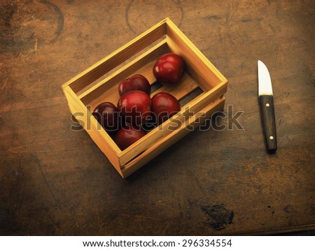 Fresh harvested plums, very ripe. In a small wooden crate. Plums on a old wooden table.  - stock photo