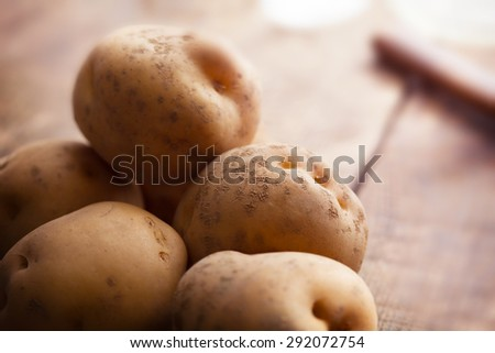 Fresh harvested potatoes spilling out of a burlap bag, on a rough wooden palette. Shallow depth of field. - stock photo