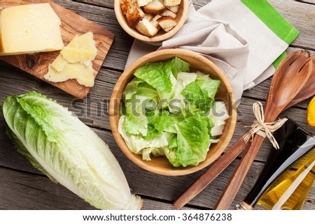 Fresh healthy caesar salad cooking on wooden table. Top view - stock photo