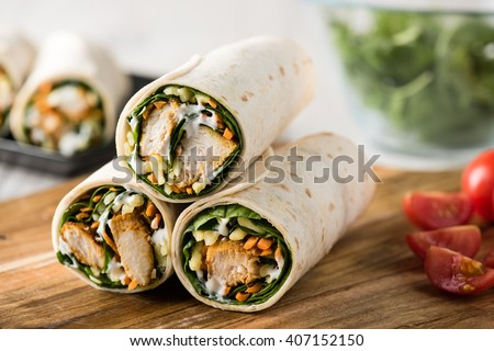 Fresh healthy chargrilled tandoori chicken wrap with tzatziki, cheese, baby spinach and carrots  - stock photo