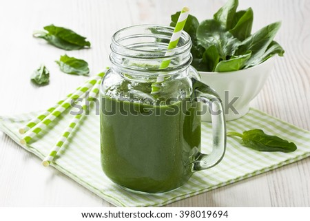 Fresh healthy green spinach smoothie in glass mason jar with straw/Spinach smoothie   - stock photo