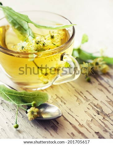 fresh healthy linden tea in cup on wooden background