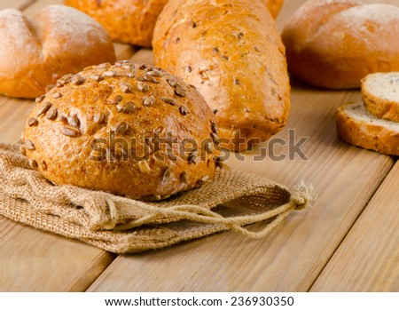 Fresh healthy natural bread on  wooden board. Selective focus - stock photo