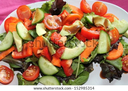 Fresh Healthy nutritious salad with avocado, cucumber, tomato, carrot and peppers - stock photo