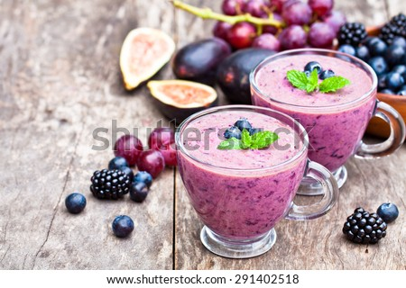 fresh healthy pulpy cocktail with purple fruits and berries - stock photo