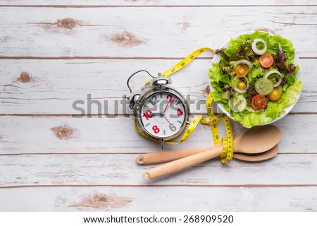 Fresh healthy salad and measuring tape on wooden table. Healthy food - stock photo