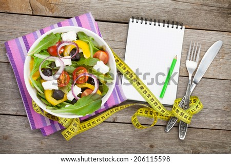 Fresh healthy salad and notepad for copy space and silverware on wooden table. View from above - stock photo