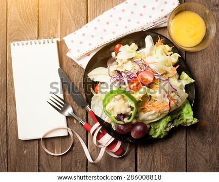Fresh healthy salad and notepad on wooden table. View from above - stock photo