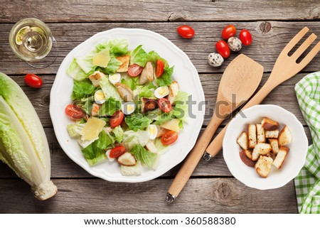 Fresh healthy salad and white wine on wooden table. Top view - stock photo