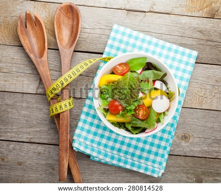 Fresh healthy salad on wooden table and kitchen utensil. View from above with copy space - stock photo