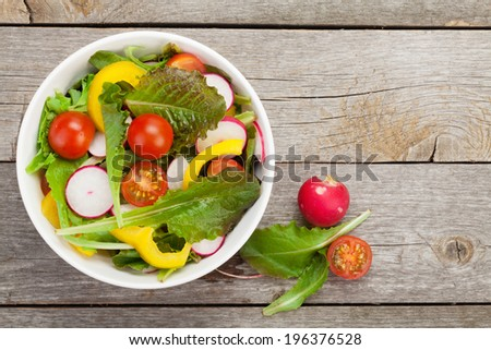 Fresh healthy salad on wooden table. View from above with copy space - stock photo
