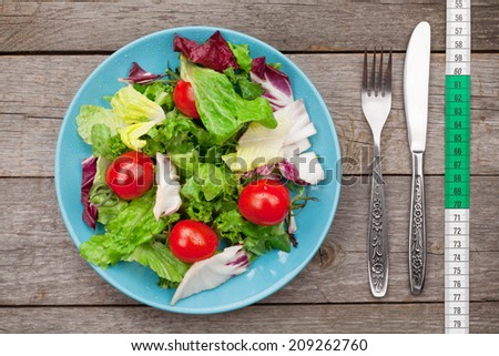 Fresh healthy salad, tomatoes and utensils on wooden table. Healthy food - stock photo