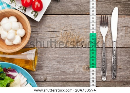 Fresh healthy salad, tomatoes, mozzarella on wooden table. Healthy food - stock photo