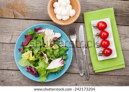 Fresh healthy salad, tomatoes, mozzarella on wooden table. Healthy food - stock photo