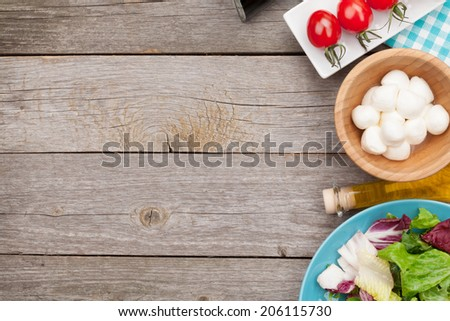 Fresh healthy salad, tomatoes, mozzarella on wooden table with copy space - stock photo