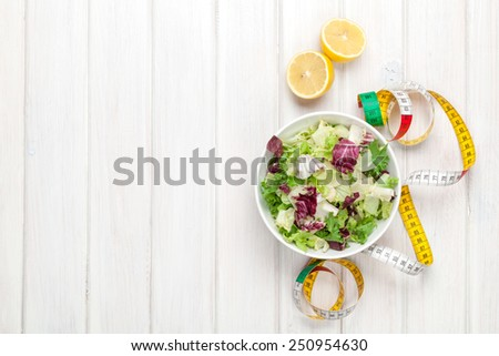 Fresh healthy salad, utensils and tape measure over white wooden table. View from above with copy space  - stock photo