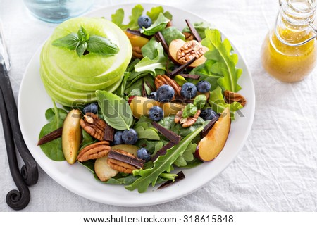 Fresh healthy salad with leafy greens, plums, nuts and apple - stock photo