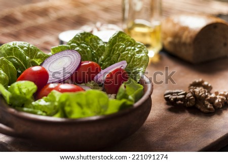 Fresh healthy salad with lettuce, tomato, onions and walnuts. Rustic wooden table background. - stock photo