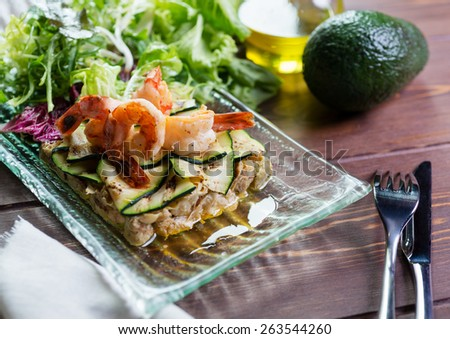 Fresh healthy salad with shrimps and vegetables serving on the plate on a wooden table in a restaurant with decor - stock photo