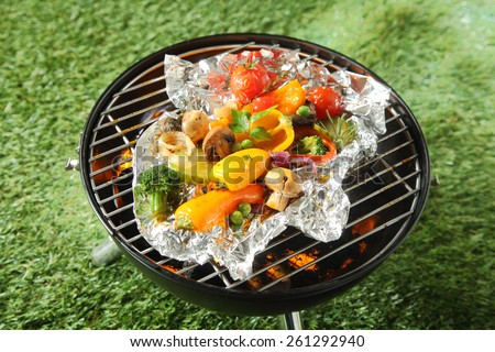 Fresh healthy selection of grilled vegetables cooked in foil over a BBQ including broccoli, peas, onion, sweet pepper, mushroom, and tomato - stock photo