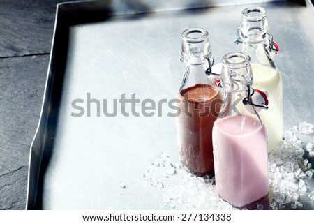 Fresh healthy smoothies or milkshakes served in glass bottles with berry, chocolate and vanilla flavours served on a metal tray with copyspace - stock photo