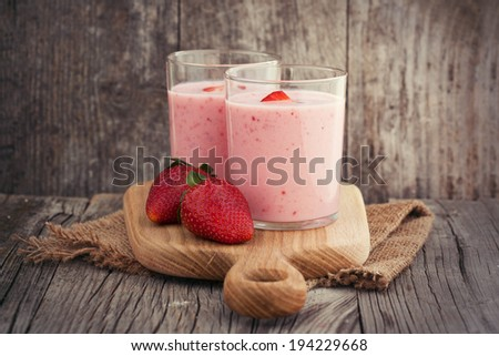 Fresh healthy strawberry smoothie on old wooden background - stock photo