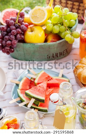 Fresh healthy tropical fruit on a picnic blanket on the grass with sliced watermelon on sticks and a bowl of grapes, apple, grapefruit, orange and banana - stock photo