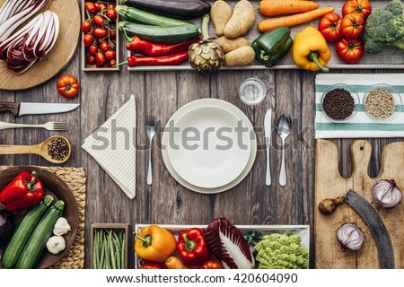Fresh healthy vegetables, chopping boards and cooking utensils composing a frame on a vintage kitchen worktop, table set at center - stock photo