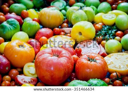 Fresh heirloom tomatoes background, organic produce at a Farmer's market - stock photo