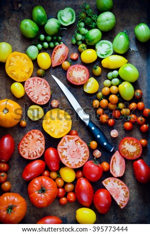 Fresh heirloom tomatoes with knife, organic produce at a Farmer's market - stock photo