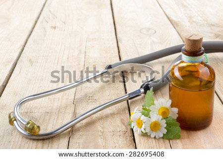 Fresh herb and stethoscope on wooden table. Alternative medicine concept. - stock photo