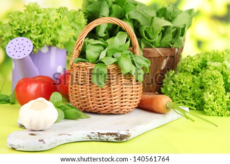 Fresh herb in basket on wooden table on natural background - stock photo