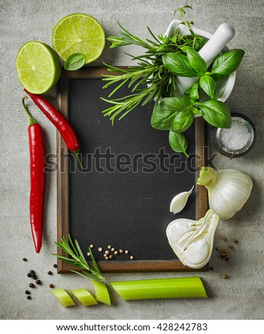 fresh herbs and spices and blackboard on gray kitchen table, top view