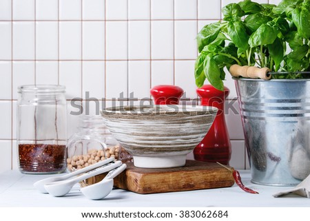 Fresh herbs Basil and Parsley in metal pots and ceramic bowl of raw chick-pea over kitchen table with white tiled wall at background.
