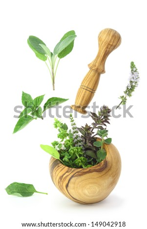 Fresh herbs falling into a wooden mortar - stock photo