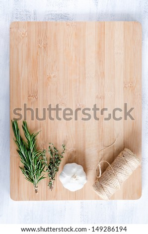 fresh herbs, garlic and twine roll on bamboo chopping board from overhead, cooking background - stock photo