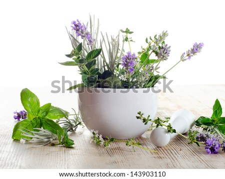 Fresh herbs on a wooden table isolated on white - stock photo