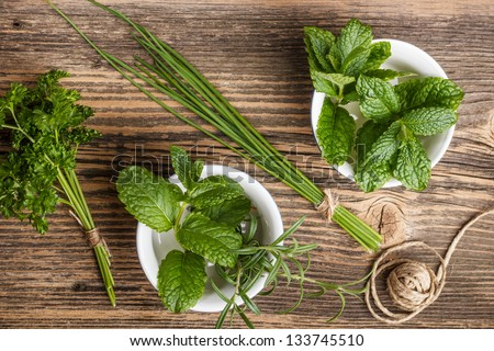 Fresh herbs on rustic wooden background - stock photo