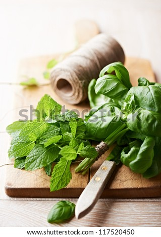 Fresh herbs on wooden chopping board - stock photo